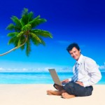 TaxConnections Picture - Man On Beach With Laptop - square