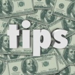 Tips word in white 3d letters on a background of hundred dollar bills in cash money as a bonus, thank you or appreciation of excellent service
