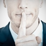 Top secret! - Young businessman with finger on his lips